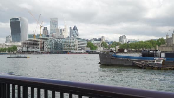 Left to right pan of downtown London skyline, boats floating on River Thames
