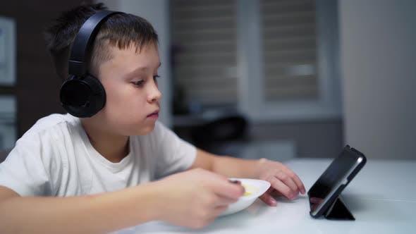 Junge isst in der Küche. Porträt eines Jungen, der während des Mittagessens ein digitales