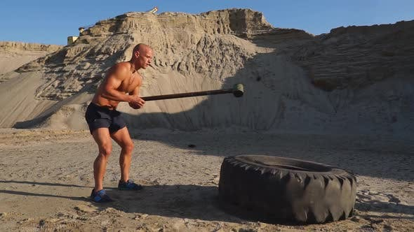Thumbnail for Bald Man Strongman Hits a Hammer on a Huge Wheel in the Sandy Mountains in Slow Motion