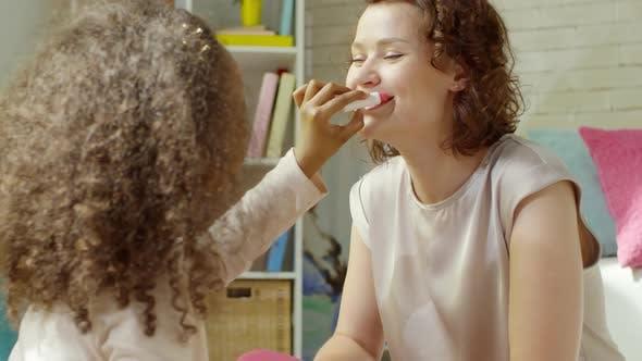 Little African Girl Applying Lipstick to Female Teacher in Kindergarten