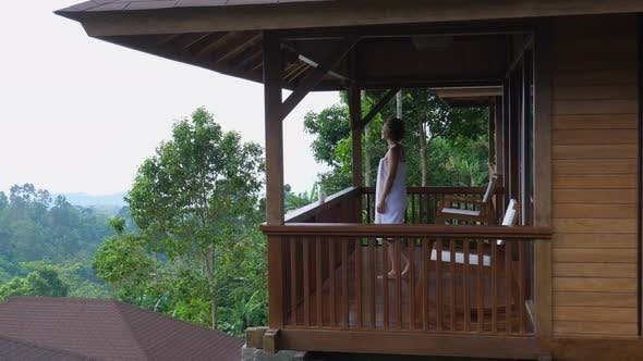 Side View of a Balcony of a Country House with a Woman Wrapped with White Towel Around Her Entering
