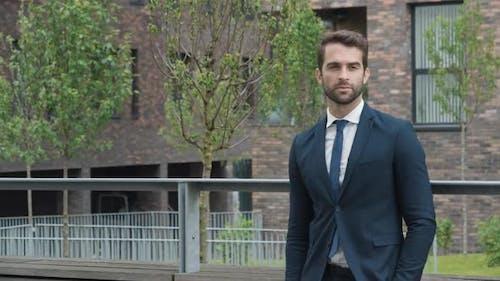 Handsome Businessman Buttoning Jacket