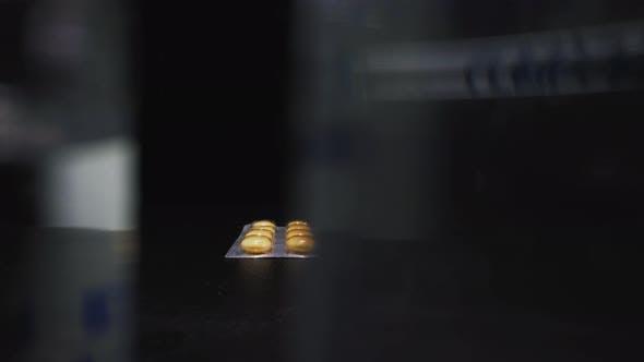 Thumbnail for Motion Along Ampules Row Hiding Yellow Pills and Syringe