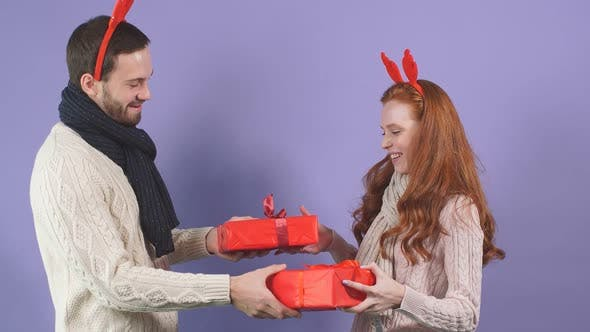 Attractive Young Couple Is Ready To Exchange Christmas Gifts