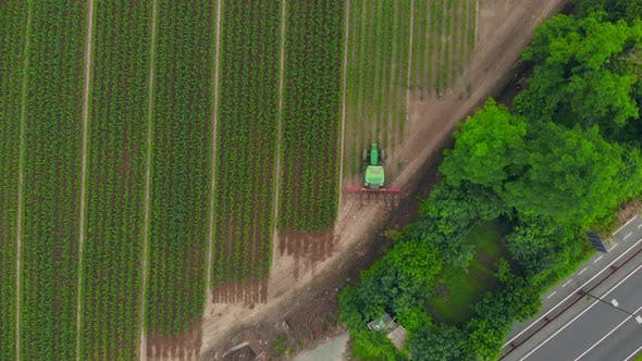 Thumbnail for Aerial: tractor working on cultivated fields farmland, inustrial agriculture occupation