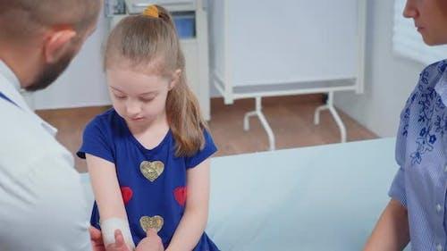 Arzt Bandaging Kind Hand