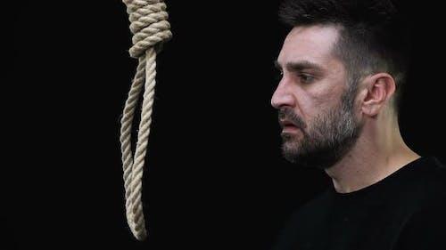 Schreckte männliche Holding Seil mit Hangmans Nelse, Suizidversuch-Prävention