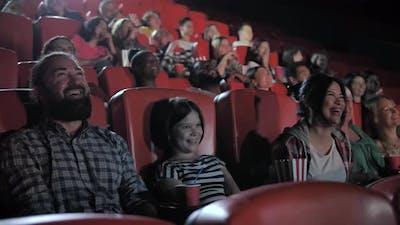 Happy Family Enjoying Comedy in Movie Theater