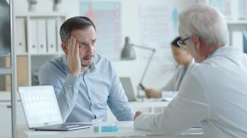 Male Patient Complaining of Headache to Doctor
