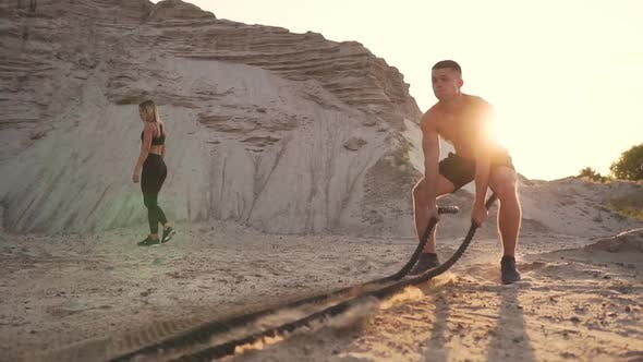 Thumbnail for Athletic Man on Exercise Around the Sand Hills at Sunset Hits the Rope on the Ground
