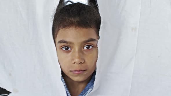 Thumbnail for Refugee Girl Standing behind Torn Cloth