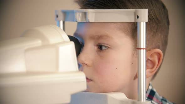 Thumbnail for A Treatment in Eye Clinic - a Little Boy Looking Through the Lens in the Device