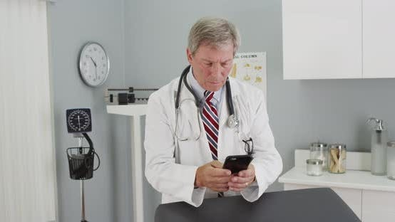 Thumbnail for Mature doctor using smartphone in the office