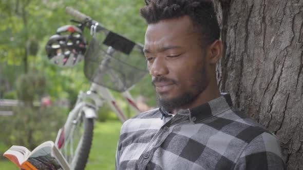 Cover Image for Portrait Confidient Cute Handsome African American Man Sitting Near His Bicycle Under an Old Tree in