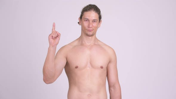 Thumbnail for Happy Muscular Shirtless Man Smiling While Pointing Up