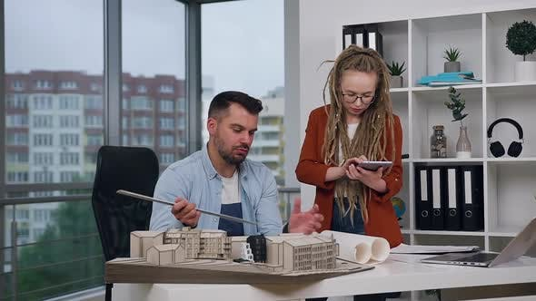 Thumbnail for Man and Woman with Dreadlocks Working Together with Mock-up of New Buildings