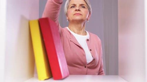 Senior Woman mit Staubwedel Reinigungsregal zu Hause