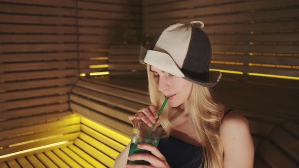 Close Up of Blonde Woman in Sauna Hat Drinking a Soft Drink From a Straw