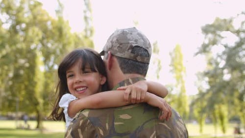 Militärvater trägt Tochter in Armen