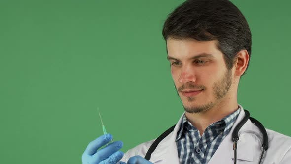 Thumbnail for Male Medical Worker Holding a Syringe on Green Background 1080p