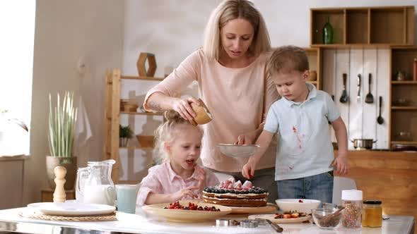 Thumbnail for Caucasian Mom Dusting Cake with Icing Sugar and Kids Watching