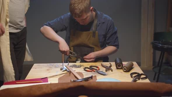 Schuhmacher überträgt Wissen an einen jungen Arbeiter
