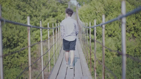 Thumbnail for Guy Walks on Suspended Bridge in the Forest
