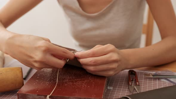 Woman making leather craft at home