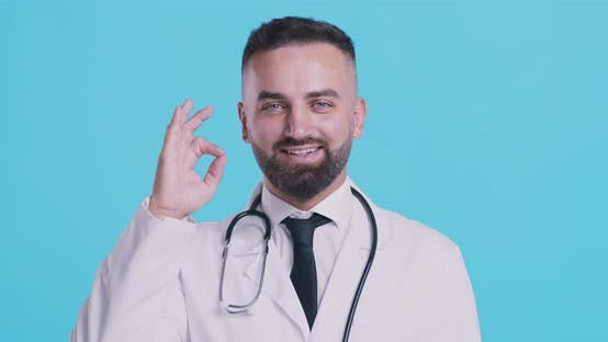 Thumbnail for Medical Doctor Showing OK Sign, Smiling Over Blue Studio Background