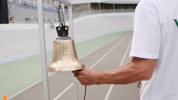 Cycling Referee Hand Rings the Bell on The Velodrome. Track Judge Ringing Golden Bell. Cycling Race