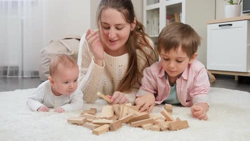 Smiling Woman Lying on Floor with Baby Boy and Older Son and Playing with Wooden Toy Blocks