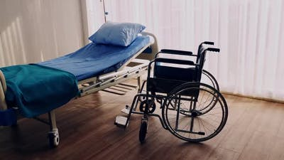 Bedroom for patient in a hospital, Empty bed and wheelchair on hospital ward