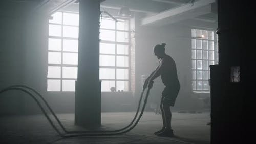 Guy Battling Ropes During Training Session
