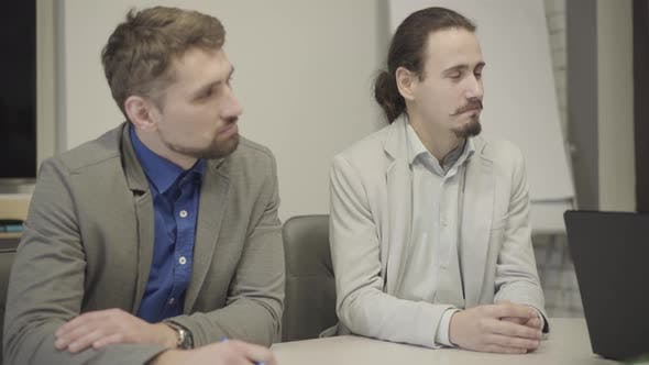 Thumbnail for Camera Approaching Two Male Caucasian Office Workers Listening Attentively As Sitting at the Table