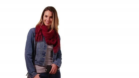 Thumbnail for Portrait of smiling millennial girl in scarf and jean jacket, standing in studio