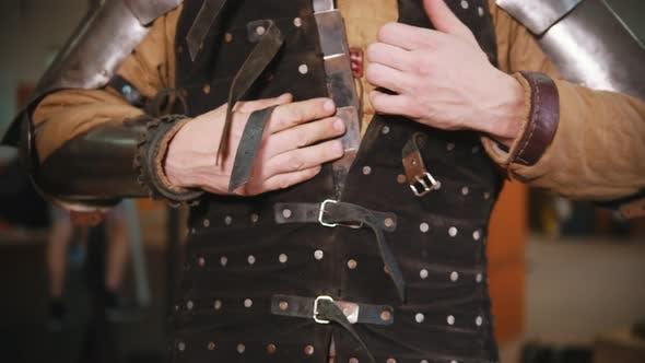 Thumbnail for Männer setzen auf ein Ritter Rüstung in der Umkleidekabine