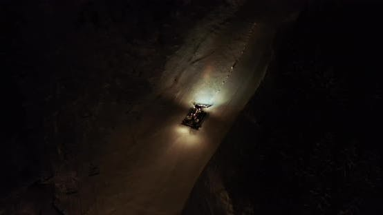 Thumbnail for Orange Illuminated Snowcat Drives Up Along White Snowy Hill on Track in Evening Darkness