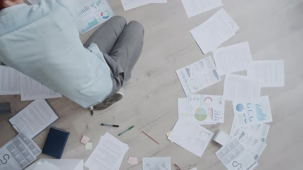 Thumbnail for Timelapse of Young Man Sitting on Floor and Working with Documents