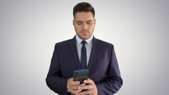 Thumbnail for Serious businessman texting message on his phone on gradient