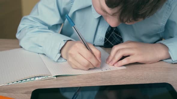 Ext CU, Tracking: Schoolboy Does Homework, Writes a Pen in a Notebook, on the Table Is a Tablet.
