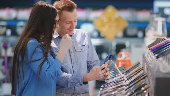 Thumbnail for The Couple Chooses a Mobile Phone in an Electronic Store. Showcase with Smartphones