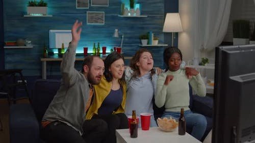 Group of Multiracial People Cheering Football Team While Sitting on Couch