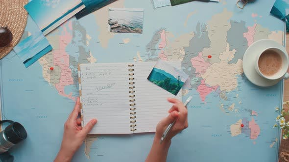Woman Writing in Notebook About Trip