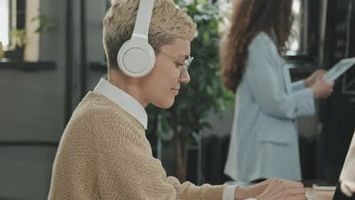 Young Woman in Headphones at Coworking Office
