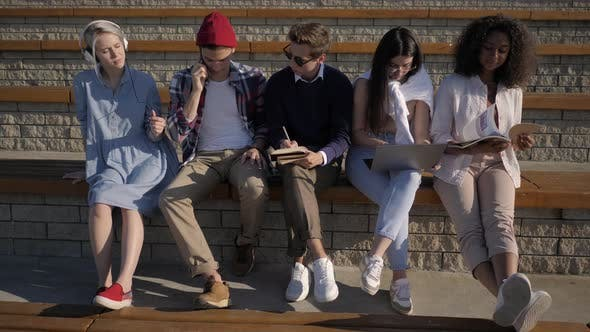 Thumbnail for Five Friends Sitting Together, Each Is Busy with Another Activity: Use Your Cell Phone, Listen To