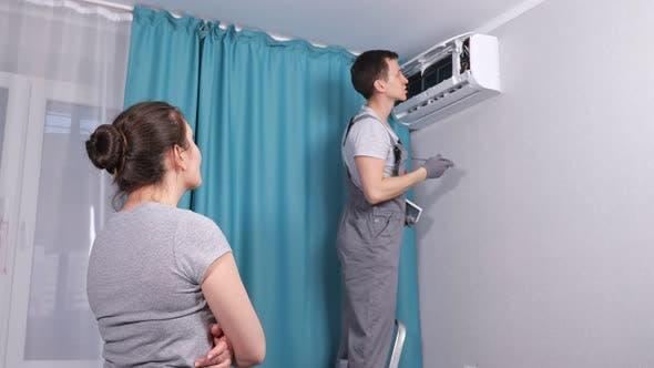 Handyman Wearing Workwear Repairs Air Conditioner in Room