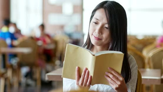 Thumbnail for Woman reading book inside coffee shop