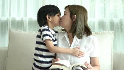 Asian Child Hugging His Mother