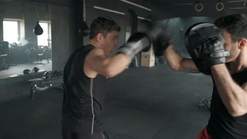 Athletischer Mann kämpft während des Trainings mit Boxtrainer im Fitnessstudio. 50Fps Footage