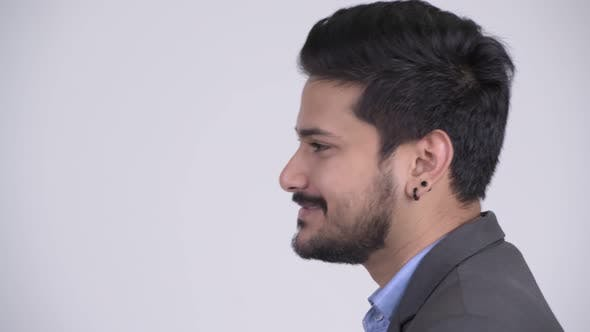 Thumbnail for Profile View of Young Happy Bearded Indian Businessman Talking
